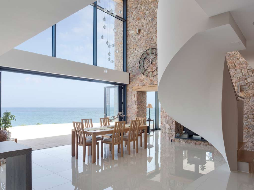 Alihaus Slide Fold Doors opening rooms of a modern home up to ocean view.