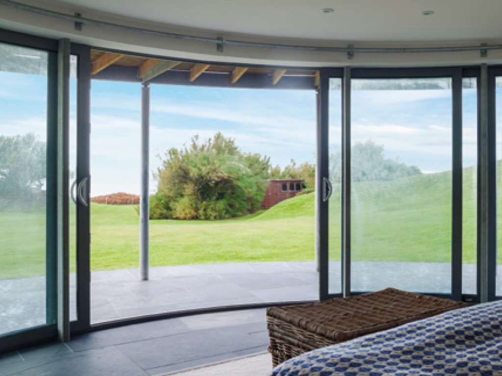 Alihaus Slide Fold Doors opening rooms of a modern home up to garden view.
