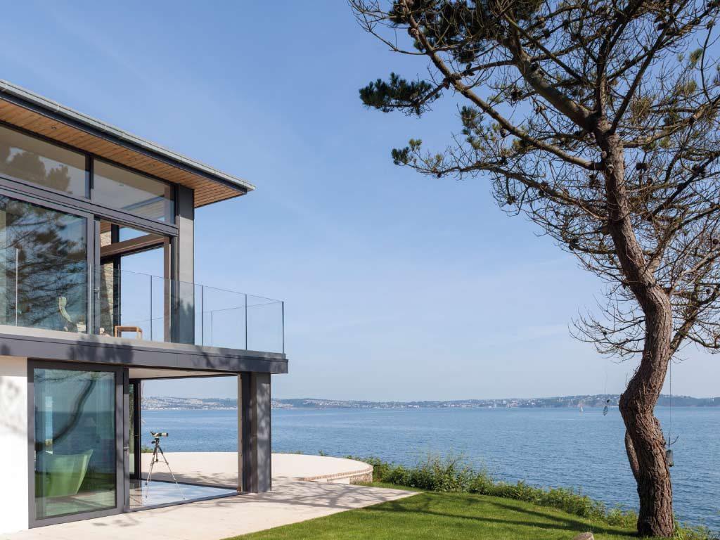 Alihaus Slide Fold Doors opening rooms of a modern home up to ocean views.